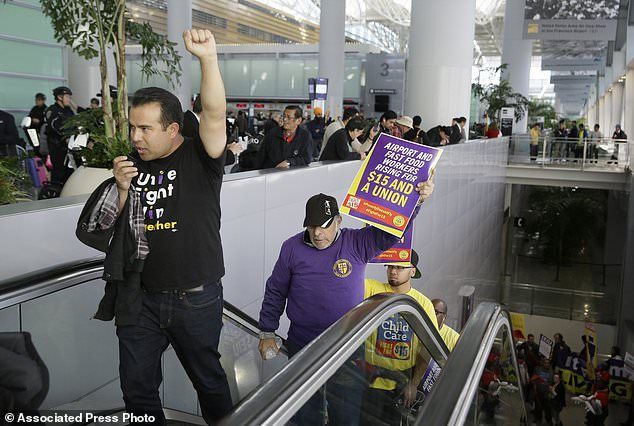 File - In this Nov. 29, 2016 file photo, workers march through the international terminal during a protest for a $15 minimum wage at San Francisco International Airport in San Francisco. The minimum wage in San Francisco increases to $15 an hour July 1, 2018, under a ballot measure approved by voters in 2014. San Francisco is the first major city in California to hit the magic $15 mark, but it won't be the last.  (AP Photo/Eric Risberg, File)