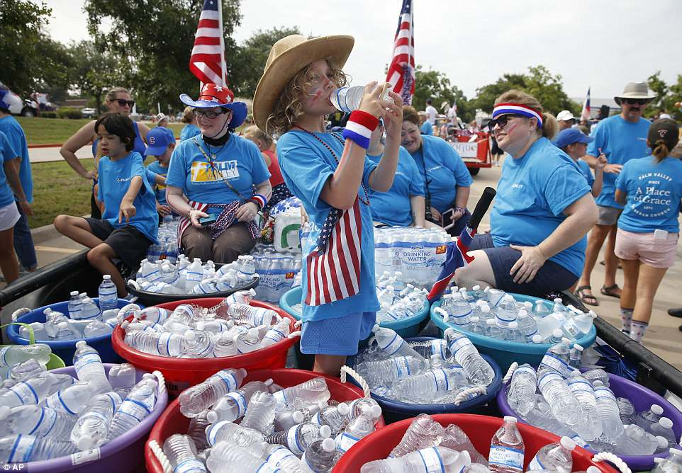 Arley Howell, six, takes a drink of water on the Palm Valley Lutheran Church float before the start of the Fourth of July parade in Round Rock, Texas