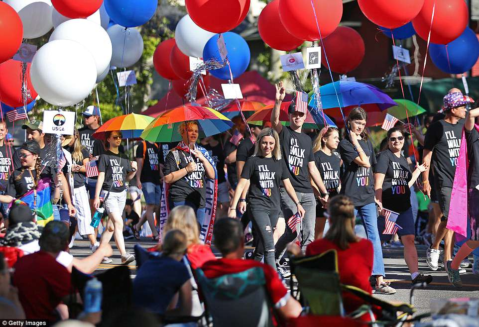 Members of the LGBT youth support group Encircle,  greet spectators as they march down Center Street in the Provo freedom Festival Pre-Parade on July 4