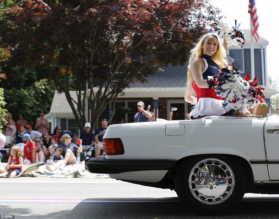 A member of the New England Patriots cheerleaders sits in the back of a convertible during the Bristol parade