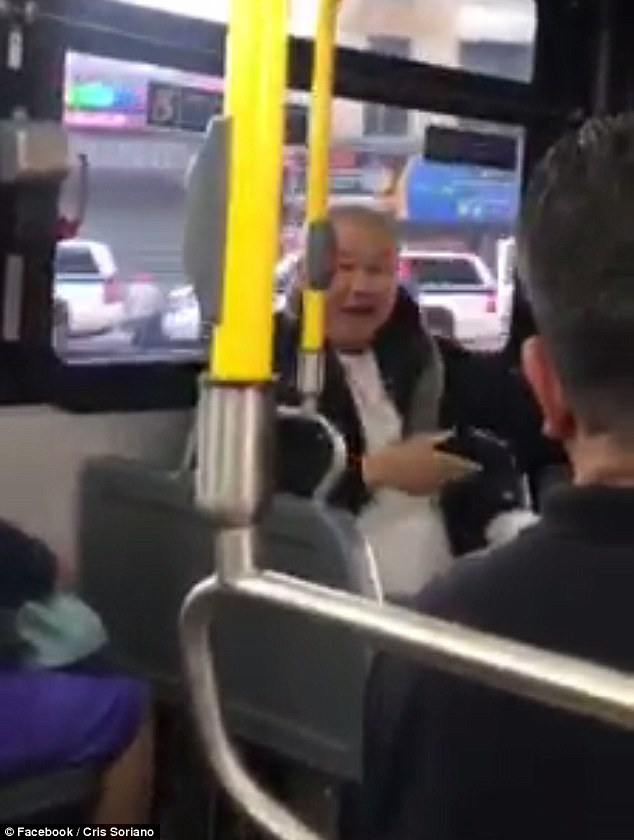 By the end of the video, the man sits down in the empty seat directly in front of the woman he has been yelling at and continues to shout with an angry look on his face