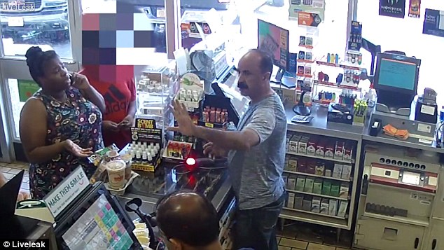 Two men behind the counter are seen speaking with the woman, who is also having a conversation on her cellphone