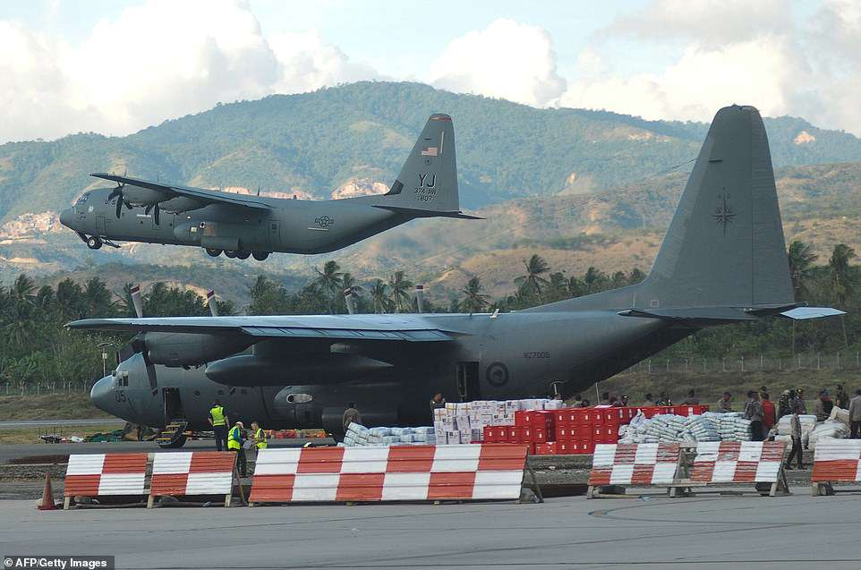 A US military aeroplane (top) leaves after sending humanitarian aid from the Mutiara SIS Al-Jufrie Airport in Palu
