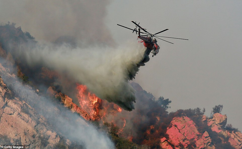 Airplanes and helicopters (pictured) swooped low over hills and canyons to drop loads of fire retardant and water