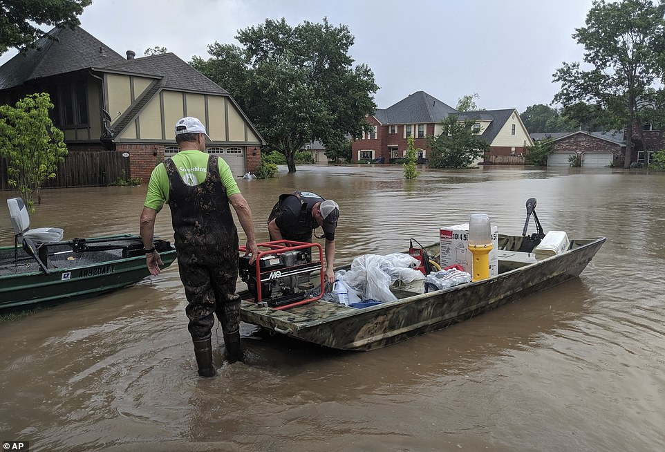 Father and son Brad and Bart Hindley, take a boat to Brad's flooded house in Fort Smith, Arkansas, on Wednesday. Brad said he doesn't live in a flood plain, but flood waters from the Arkansas River continue to rise