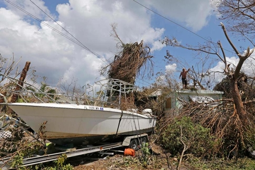 Michael Seifert throws a a branch off the roof of a house in the aftermath of Hurricane Irma, Wednesday, Sept. 13, 2017, in Big Pine Key, Fla. (AP Photo/Alan Diaz) The Associated Press